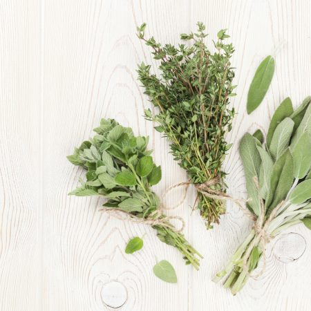 Fresh garden herbs on wooden table. Oregano, thyme, sage. Top view with copy space
