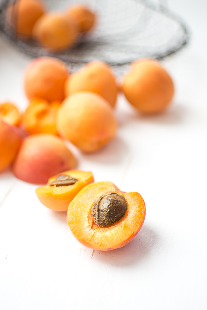 Fresh apricots, sliced in half and ready to use to make melted apricots with raspberries and pistachios.