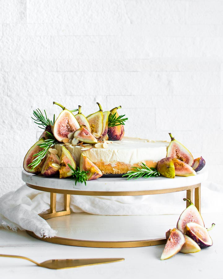 Fig tart on a marble cake stand garnished with figs, rosemary and sliced almonds.
