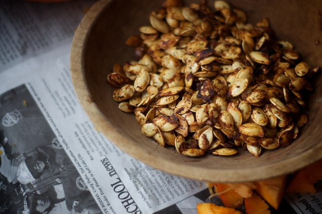 Freshly toasted pumpkin seeds sitting on newspaper.