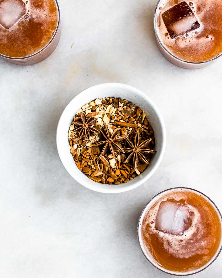 Three glasses of icy homemade root beer surrounds a small bowl filled with herbs like star anise, sarsaparilla, ginger, sassafras and licorice.
