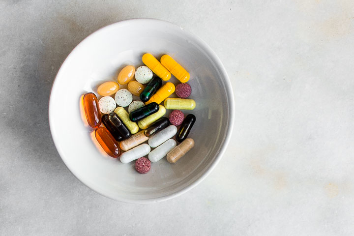 Vitamin and mineral supplements in a bowl.