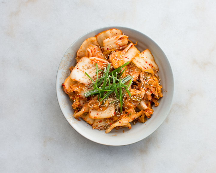 Traditionally fermented napa cabbage kimchi sits in a small dish on a marble table.