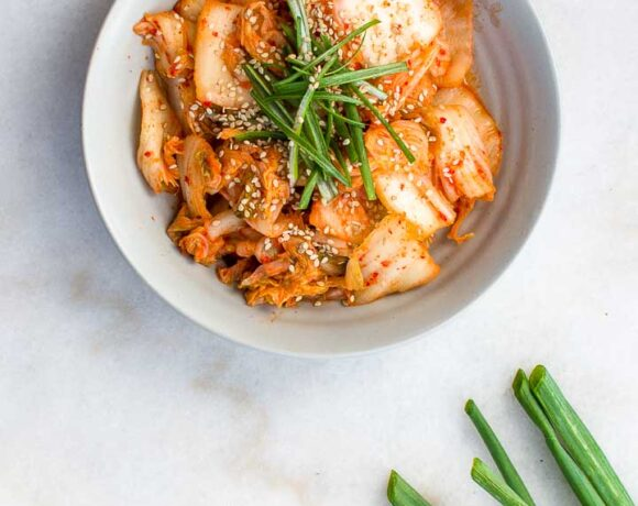 Kimchi in a stoneware bowl on a marble background, garnished with sesame seeds and green onions.