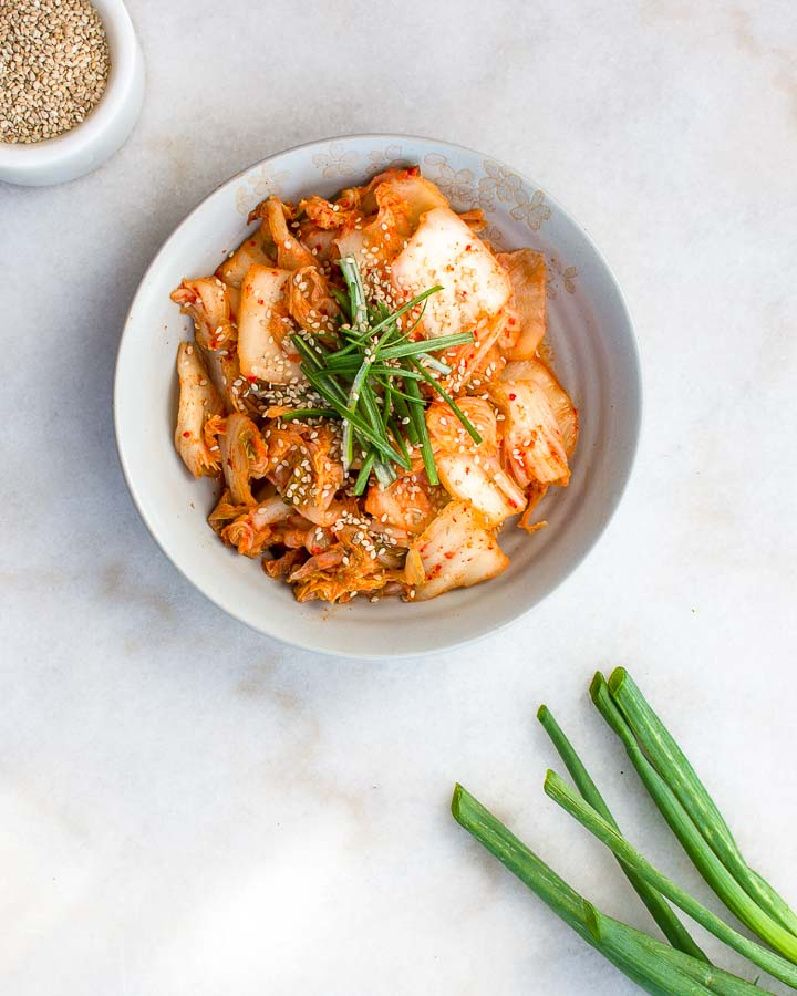 Homemade kimchi garnished by green onions and sesame seeds sits in an earthenware bowl.