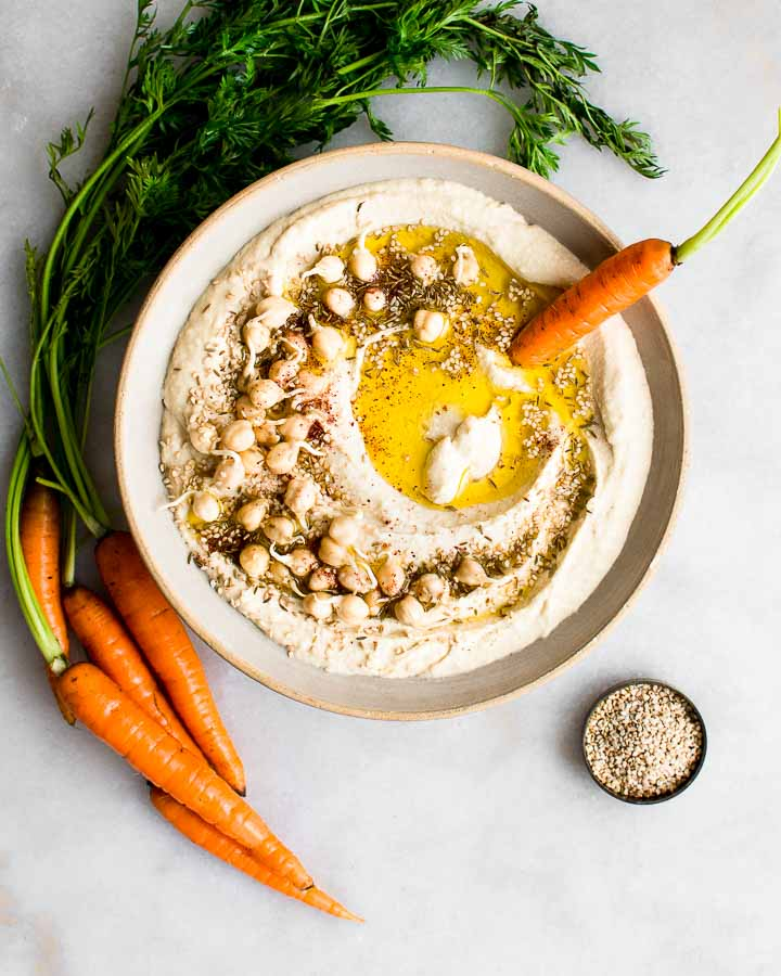 Sprouted hummus in an earthenware bowl garnished with sprouted chickpeas, cumin and sesame seeds and served with carrots.