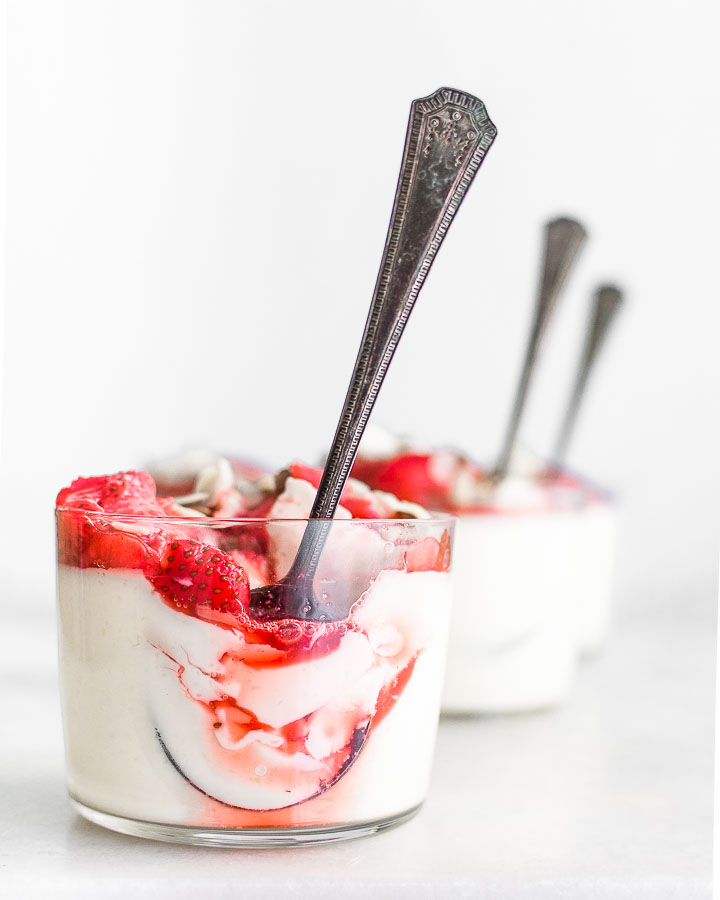 Three glasses filled with yogurt panna cotta and honey roasted strawberries.