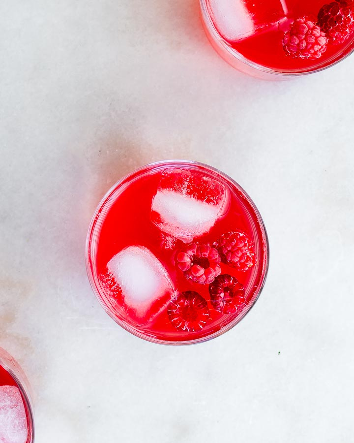 Three glasses of fermented raspberry soda served with ice and fresh raspberries.