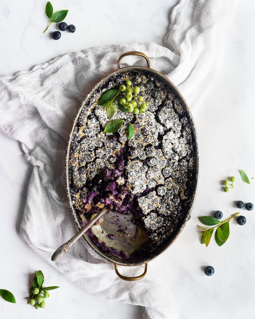 Blueberry clafoutis in a copper baking dish, dusted with powdered sugar and garnished with fresh blueberries,