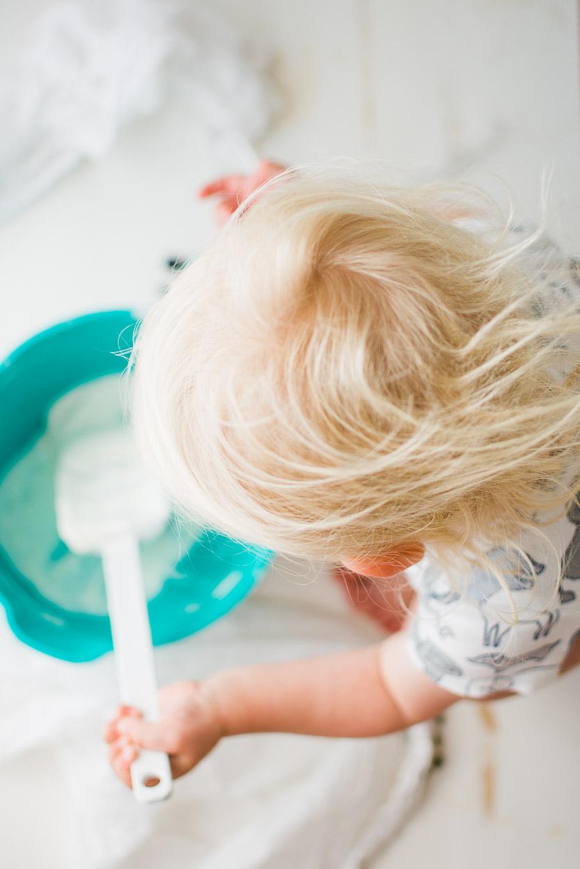 Baby mixing yogurt and honey.