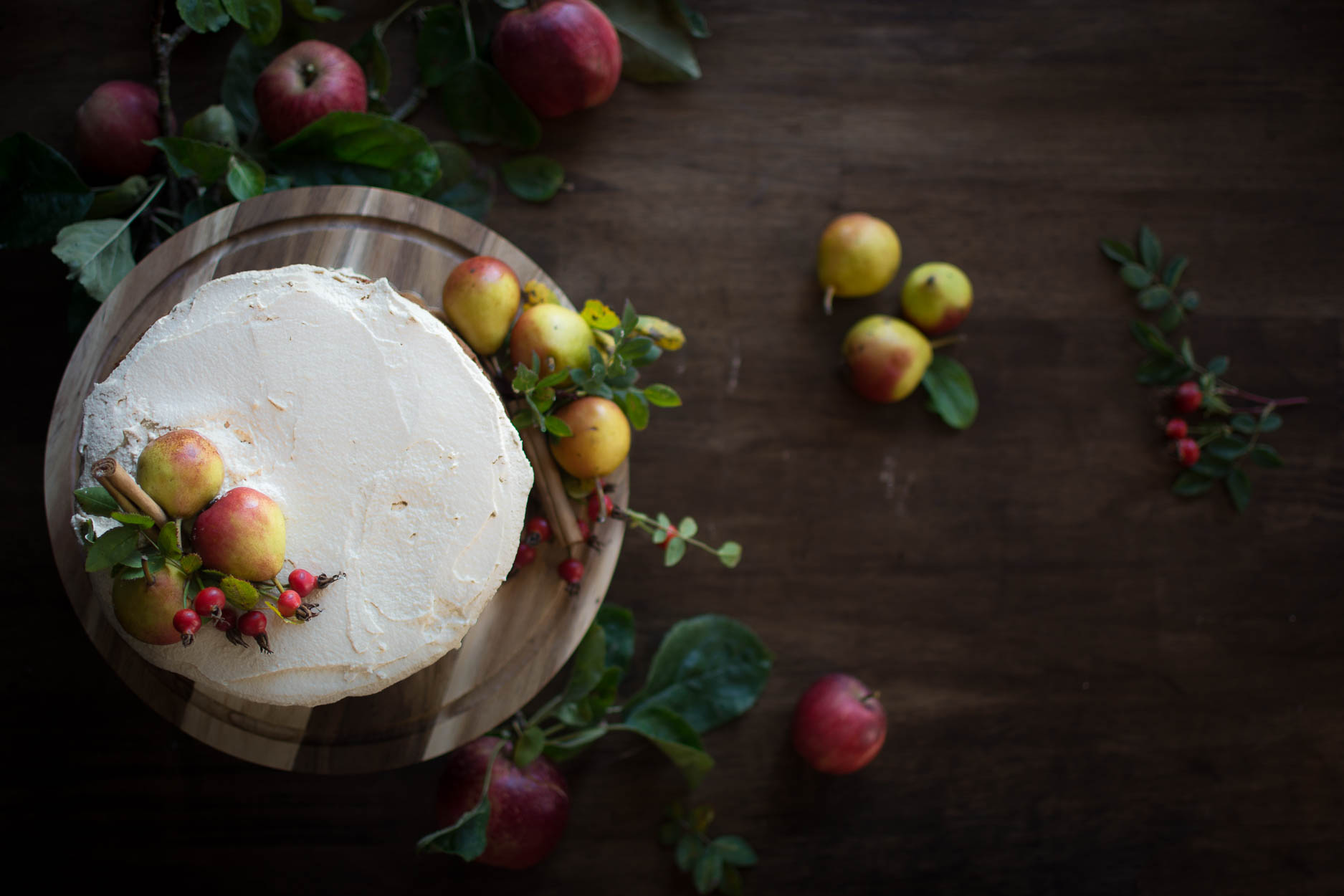 Harvest Cake with Maple Frosting decorated with apples, pears and cinnamon sticks.