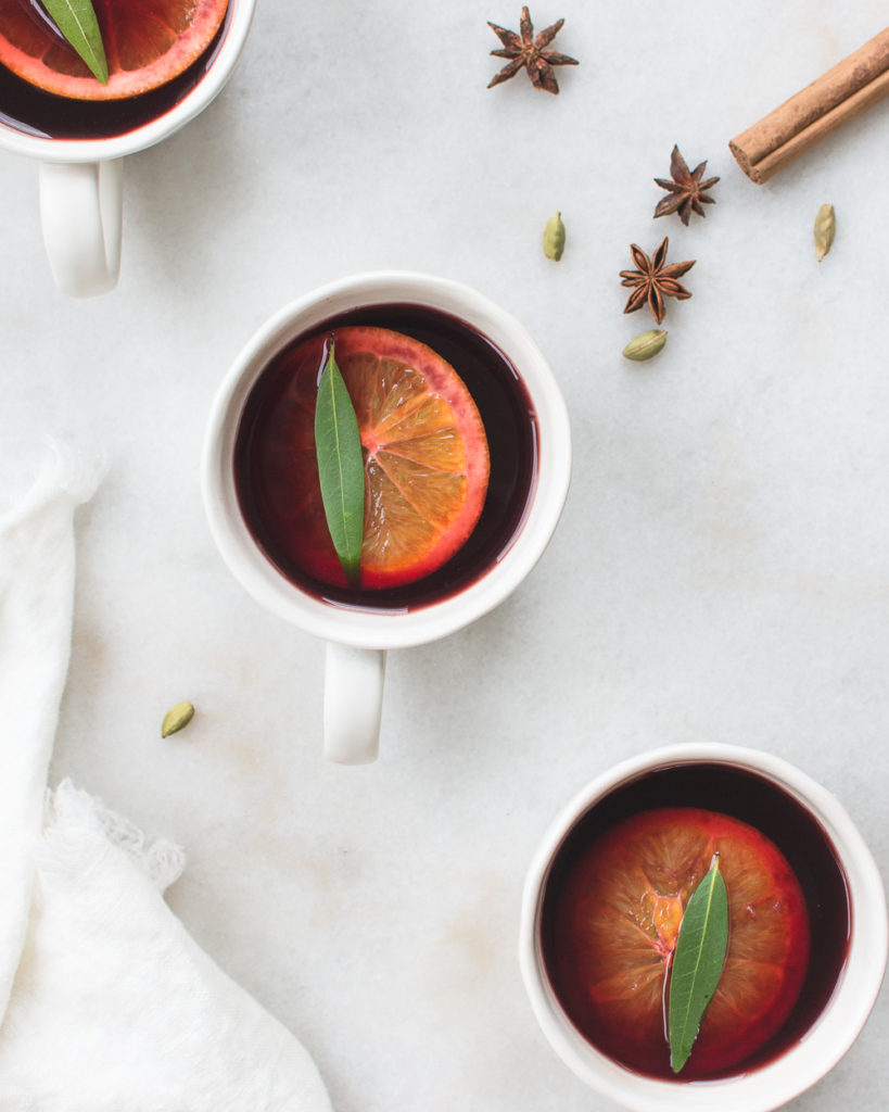 Three cups of mulled wine garnished with orange, bay leaf, and cinnamon.