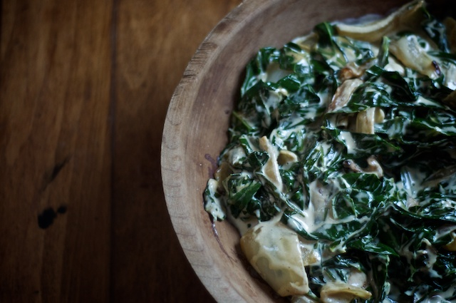 Creamed collard greens sitting in a wooden bowl on a wooden surface.