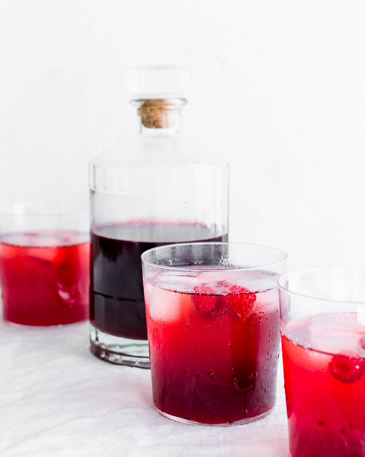 Raspberry shrub in a bottle next to three glasses.