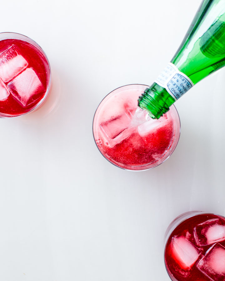 Pouring sparkling mineral water into a glass of raspberry shrub and ice.