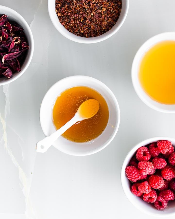 Bowls of raspberries, hibiscus flowers, rosehips, honey and apple cider vinegar.