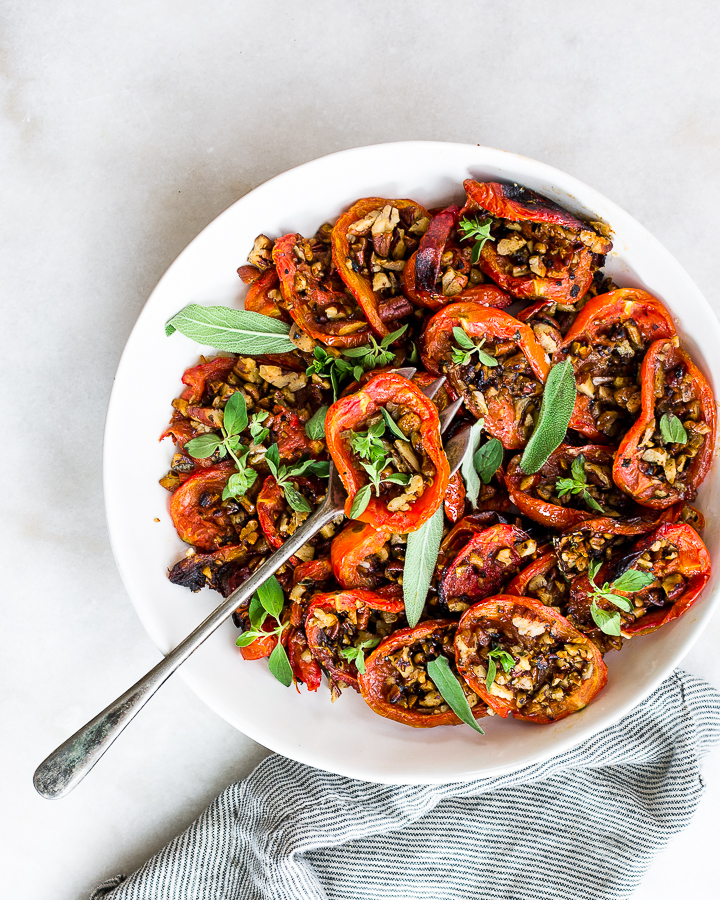 Roasted plum tomatoes with garlicky toasted pecan crumble in a white dish.