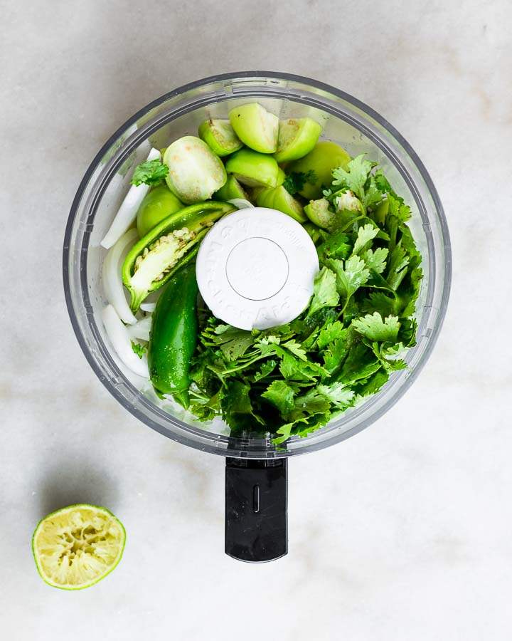 Jalapenos, cilantro, tomatillos and garlic in a food processor.