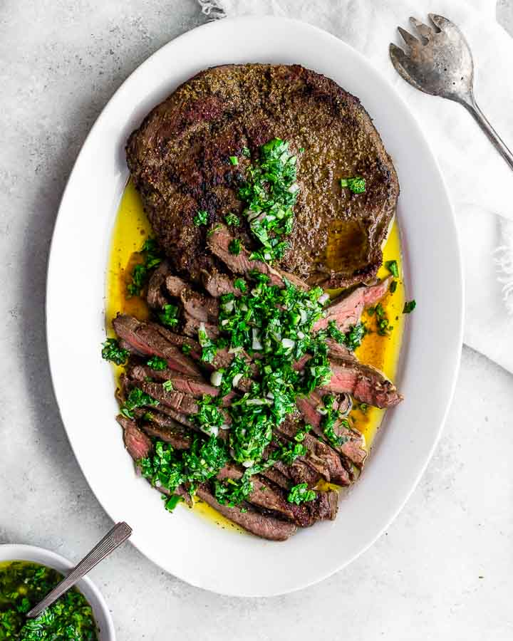 Sous vide flank steak crusted with coriander, cumin and sea salt and served on an oval plate with green herb sauce and extra virgin olive oil.