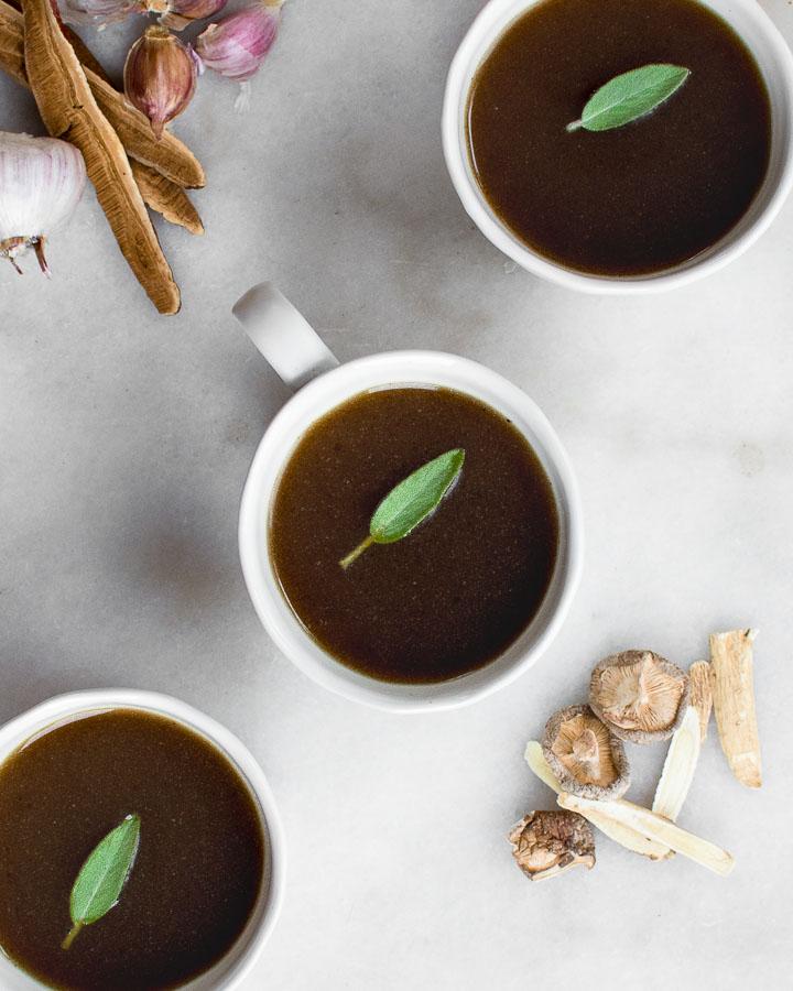 Medicinal mushroom broth in mugs, garnished by sage next to sliced reishi mushrooms, shiitakes and astragalus.