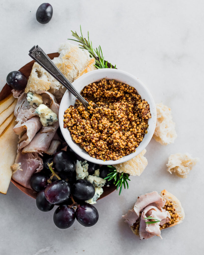 Fermented whole grain mustard in a bowl on a charcuterie platter with bread, grapes, ham, and cheese.