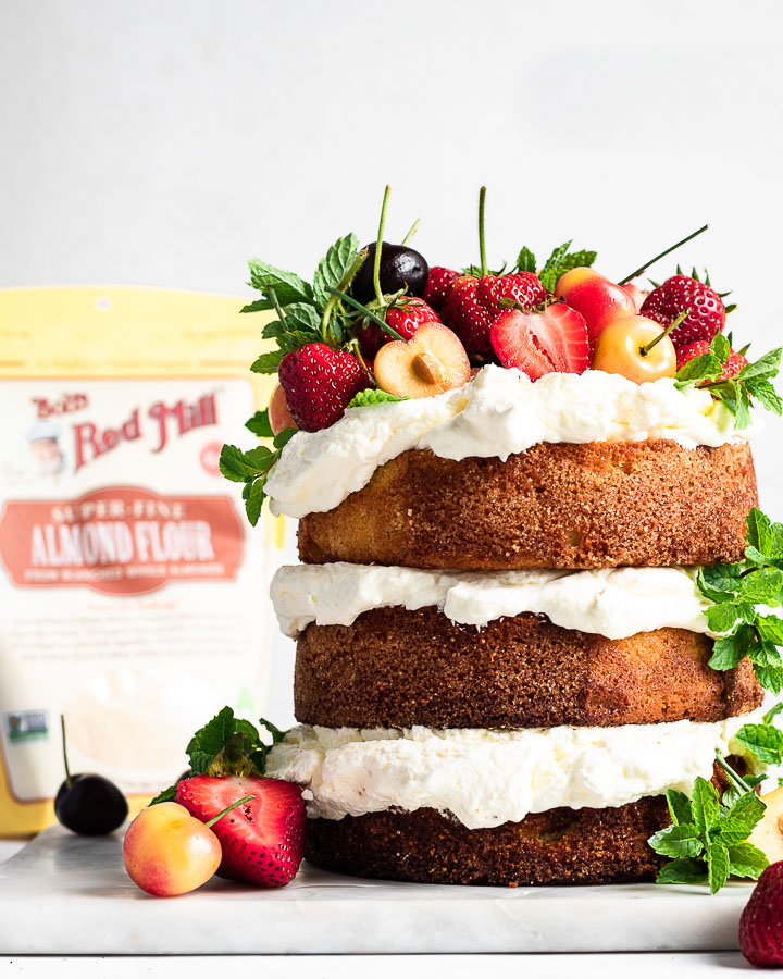 Almond flour cake topped with fruit, next to bob's red mill almond flour package.