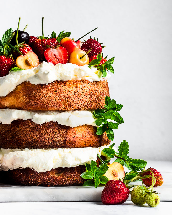 Three-layer almond flour cake topped with whipped cream, cherries, strawberries and mint.