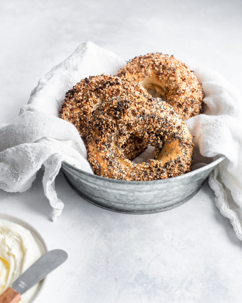 Sourdough bagels in a metal tin lined with linen.