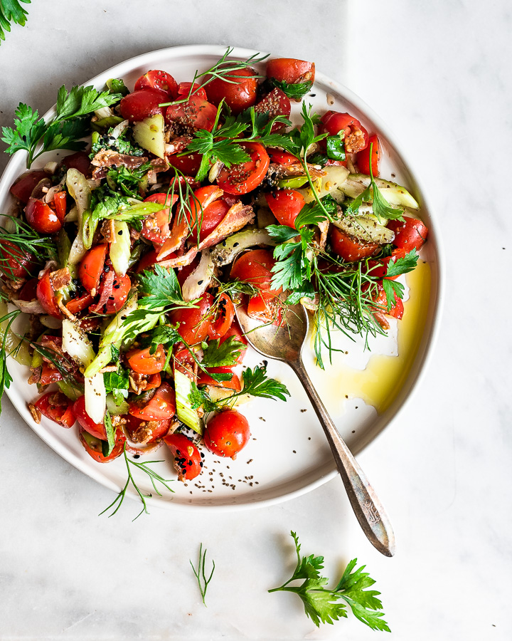 Herb-packed cherry tomato salad on a plate shot from overhead.