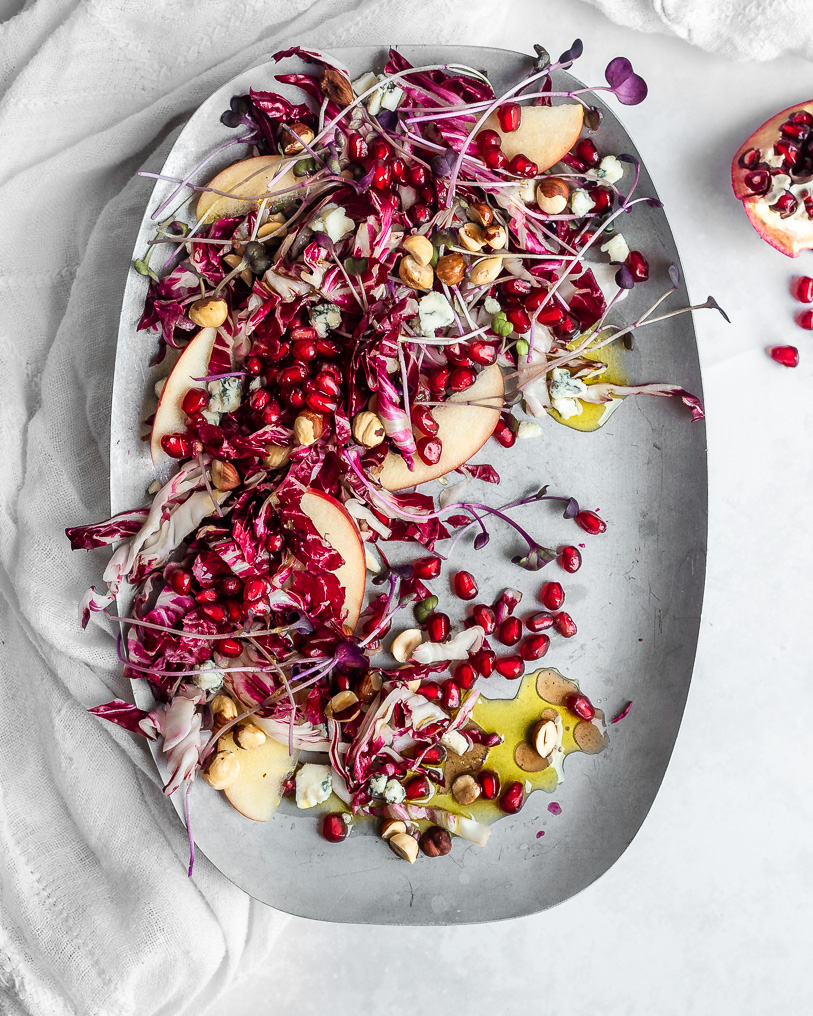 Radicchio salad with pomegranate arils, apples and hazelnuts on a pewter plate.