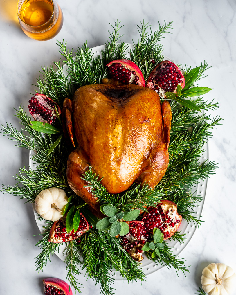 Slow-Roasted Turkey on a platter decorated with rosemary, sage, and pomegranates