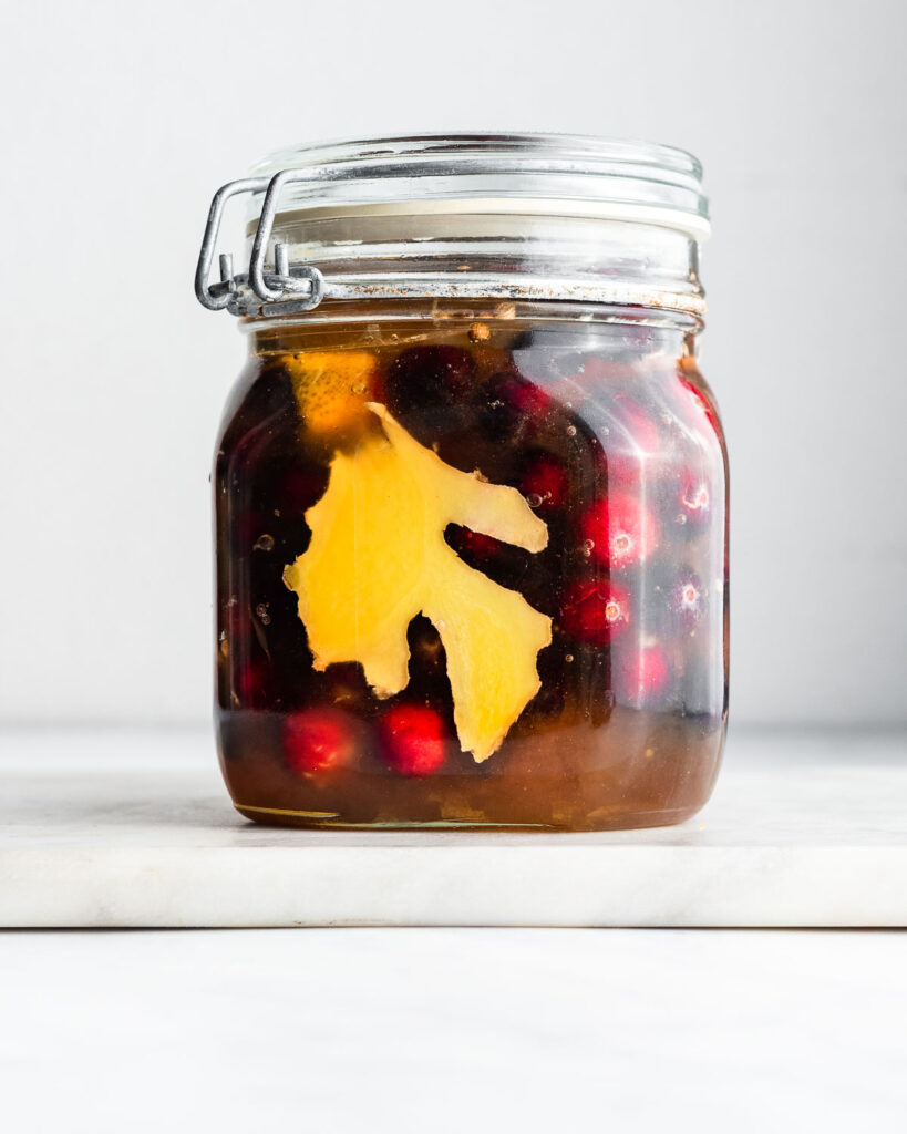 Fresh cranberries fermenting in a jar of honey with ginger, coriander, and orange peel