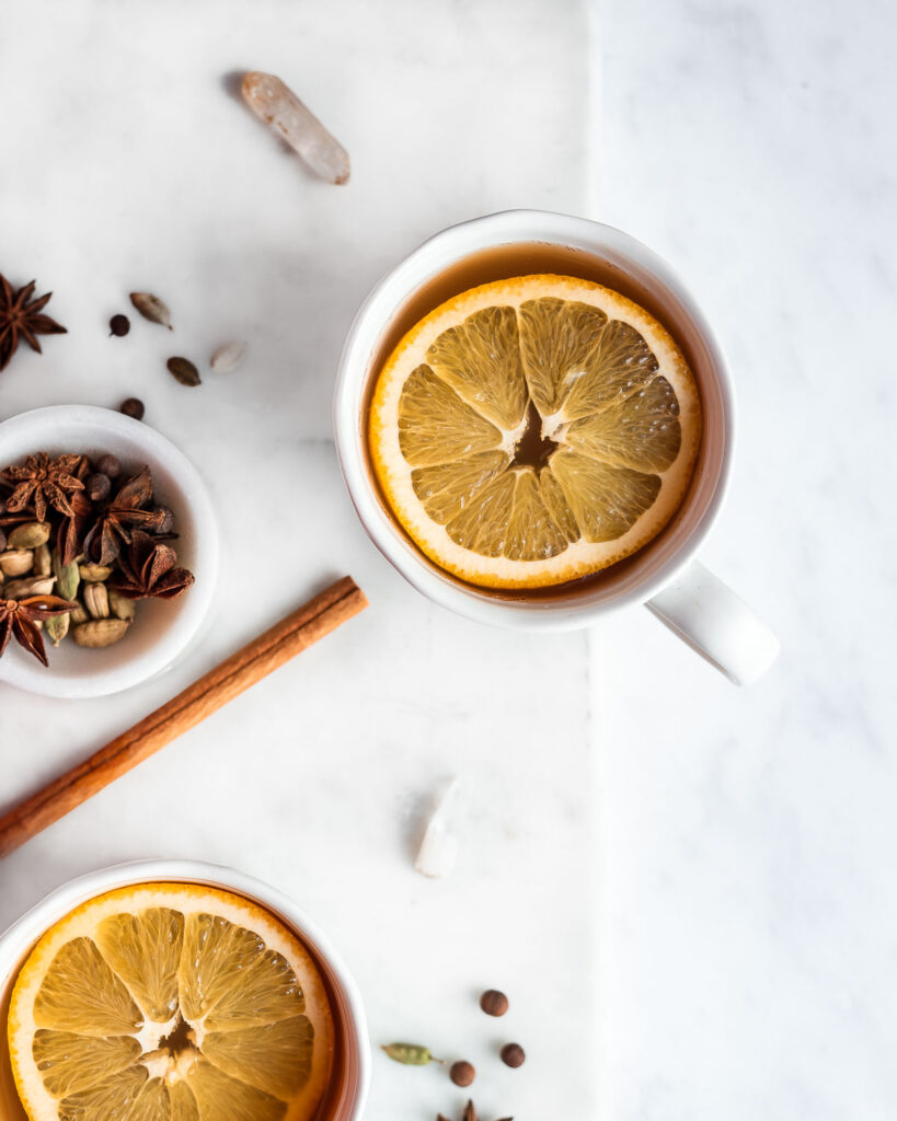 Mulled cider in two white mugs, garnished with orange slices and cinnamon stick