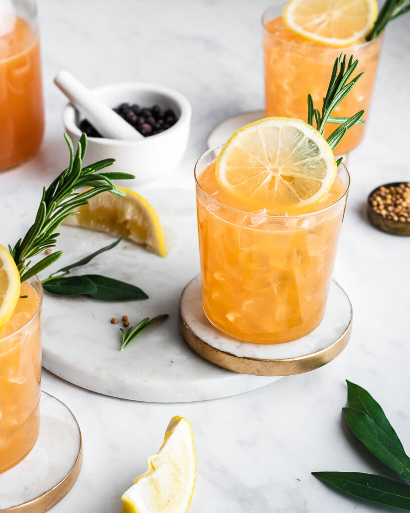 Three glasses of citrus punch garnished with lemon and rosemary.