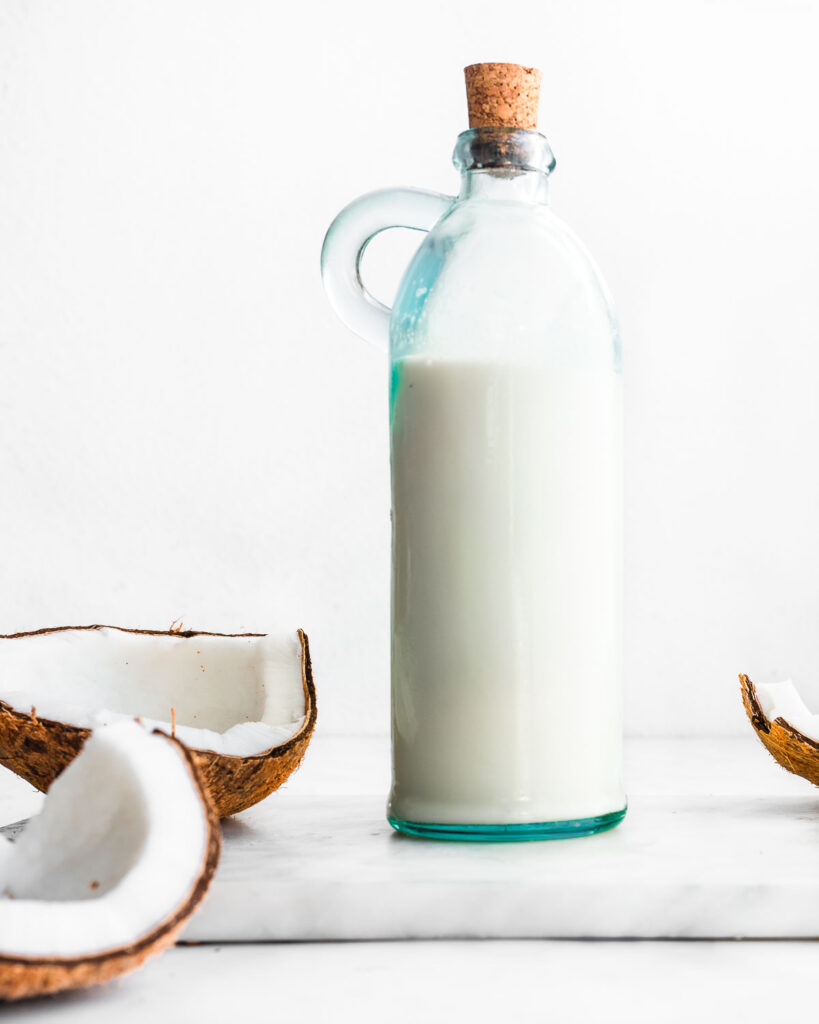 A bottle of homemade coconut milk next to a cracked brown coconut