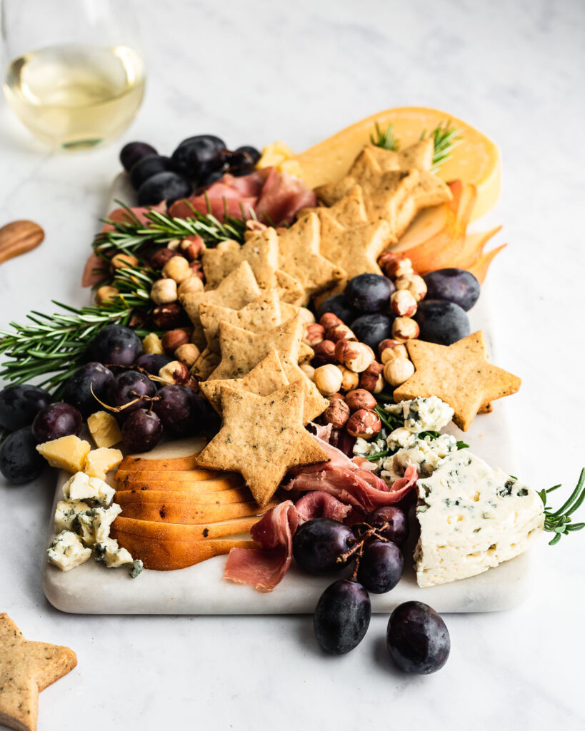 Rosemary shortbread on a charcuterie board with fruit, cheese, and hazelnuts