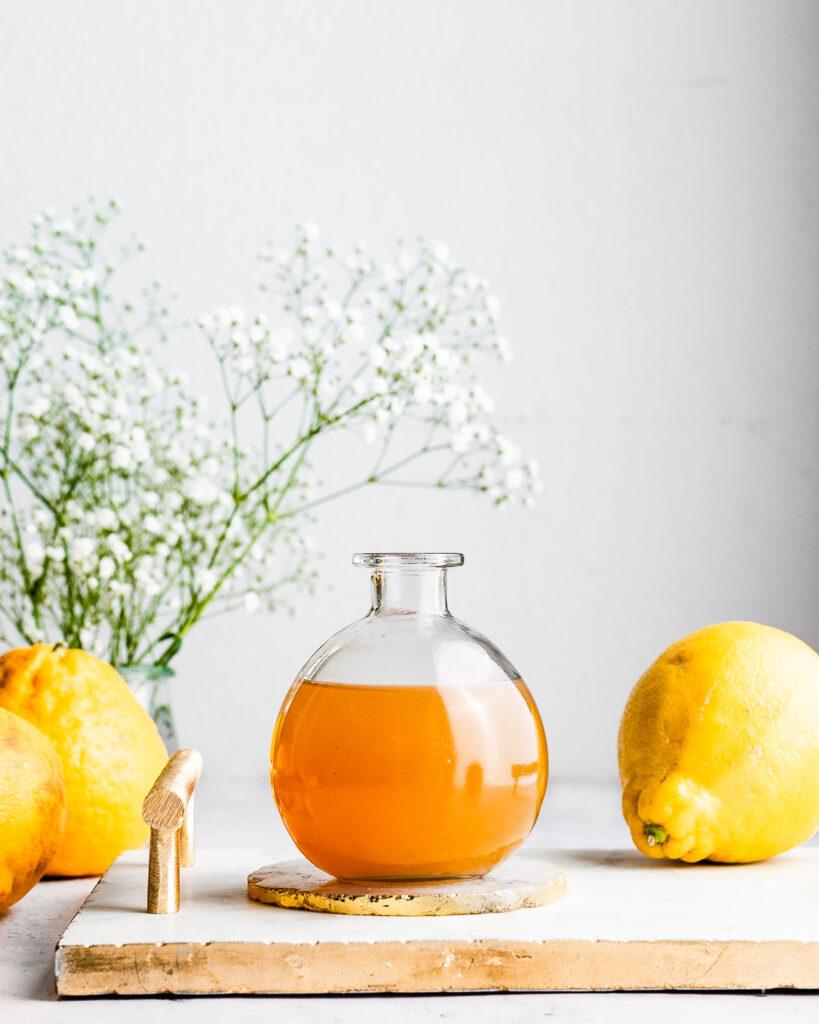 Bergamot orange syrup in a glass bottle on a tray next to fresh bergamot oranges.