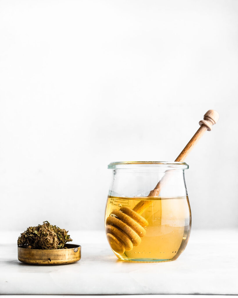 Cannabis-infused honey made with a high-CBD hemp strain in a small jar next to high-CBD hemp flower.