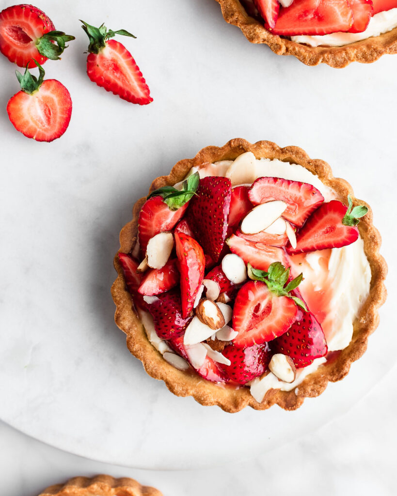 Strawberry tarts on a marble surface, garnished with sliced almonds.