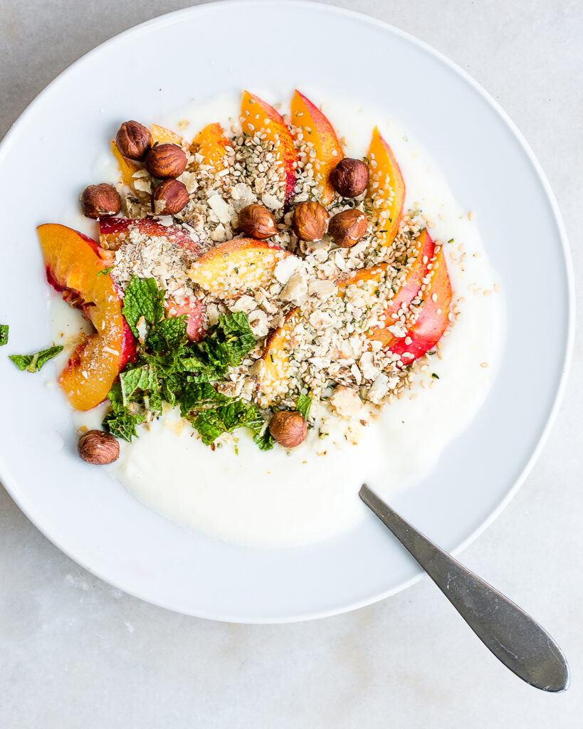 homemade yogurt in a bowl garnished with nectarines, hazelnuts, hemp seeds and mint