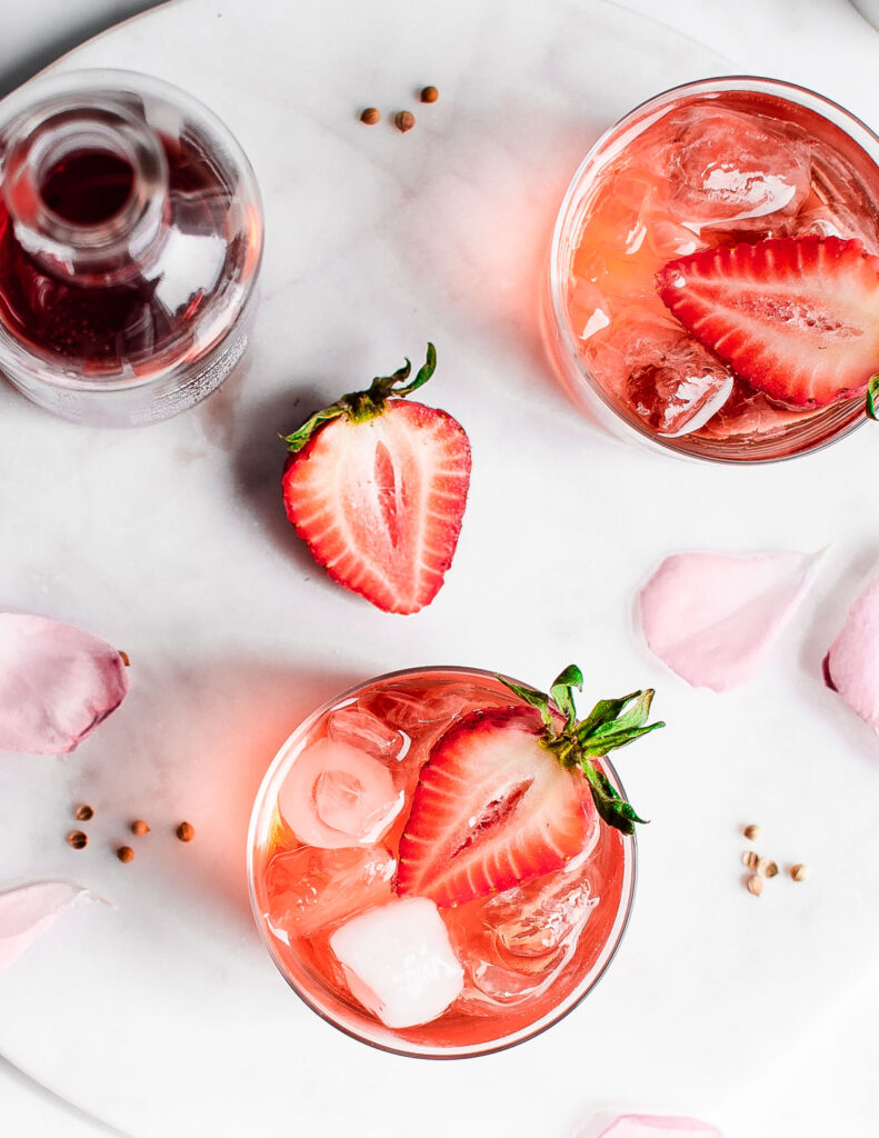 strawberry rosé smash shot from above garnished with strawberries and rose petals