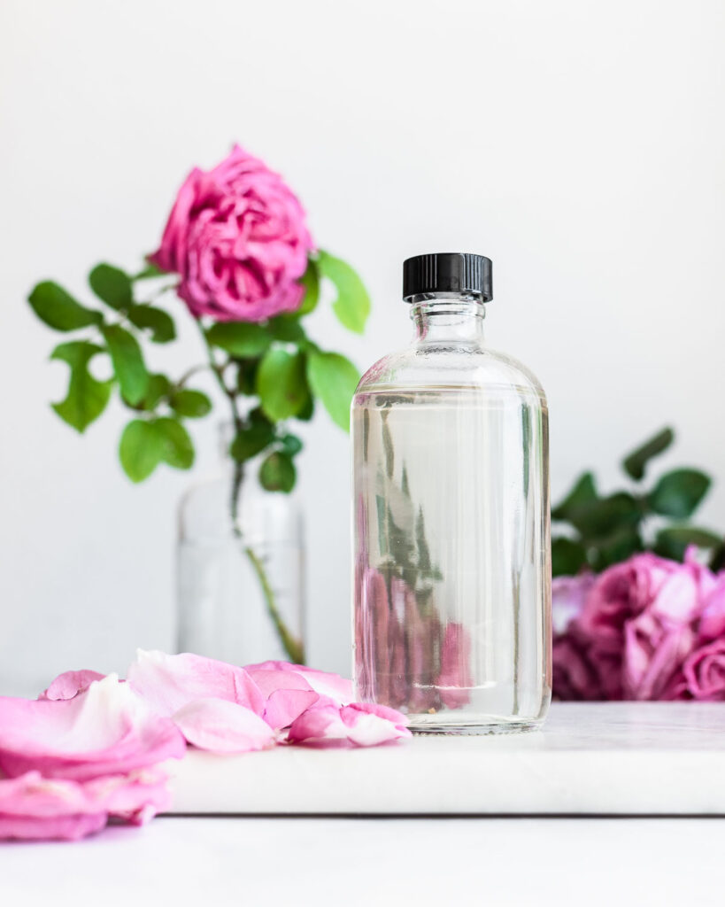Homemade rose water in a clear glass with pink Damask roses in the background