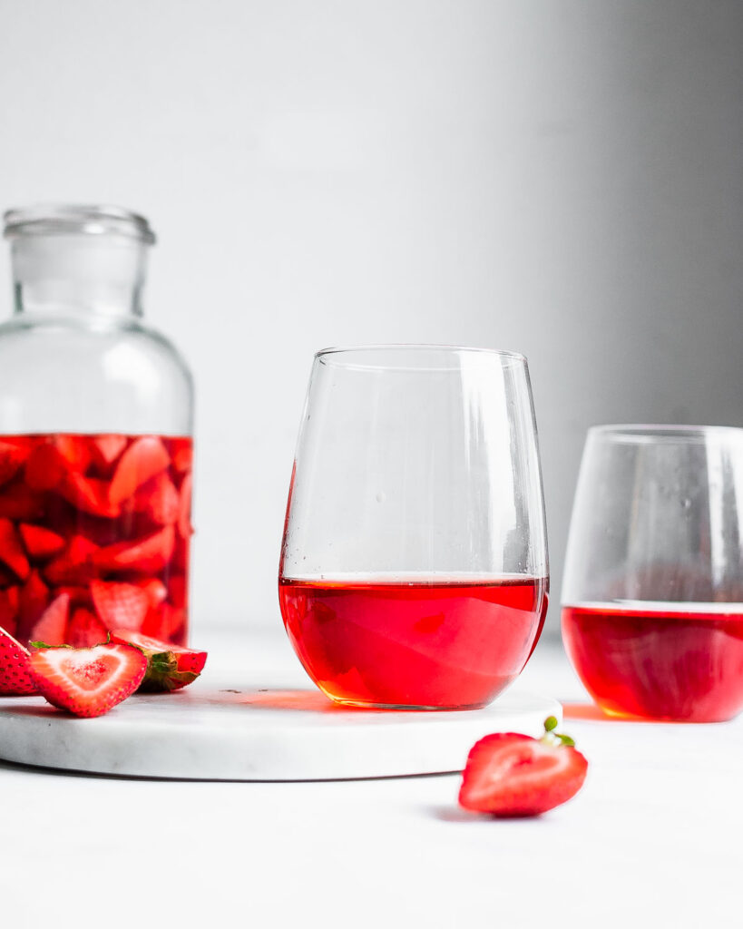 Strawberry wine in two wine glasses, garnished by fresh strawberries.