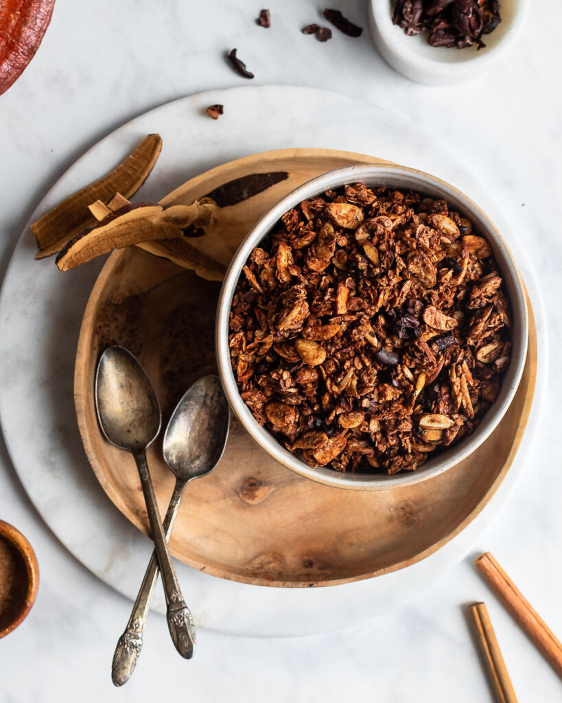 Dark chocolate granola in a bowl set on a wooden plate, garnished with cacao beans, reishi mushroom