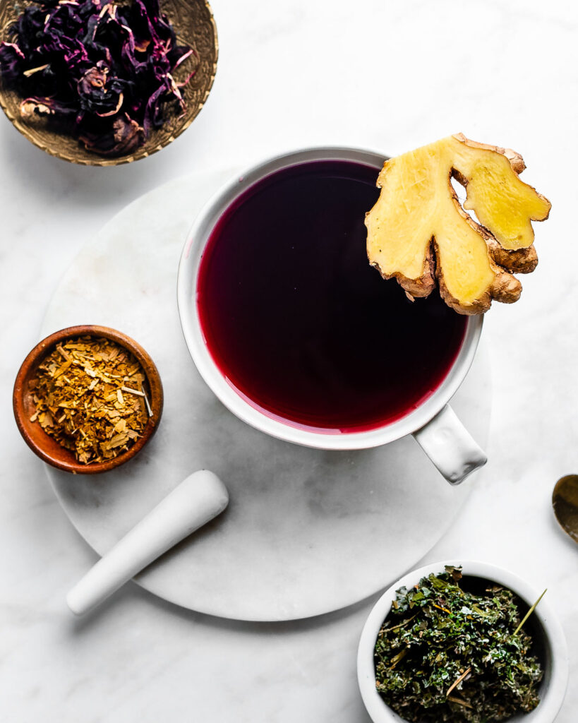 Moon tea in a large white mug, garnished with fresh ginger, red raspberry leaf, and ginkgo